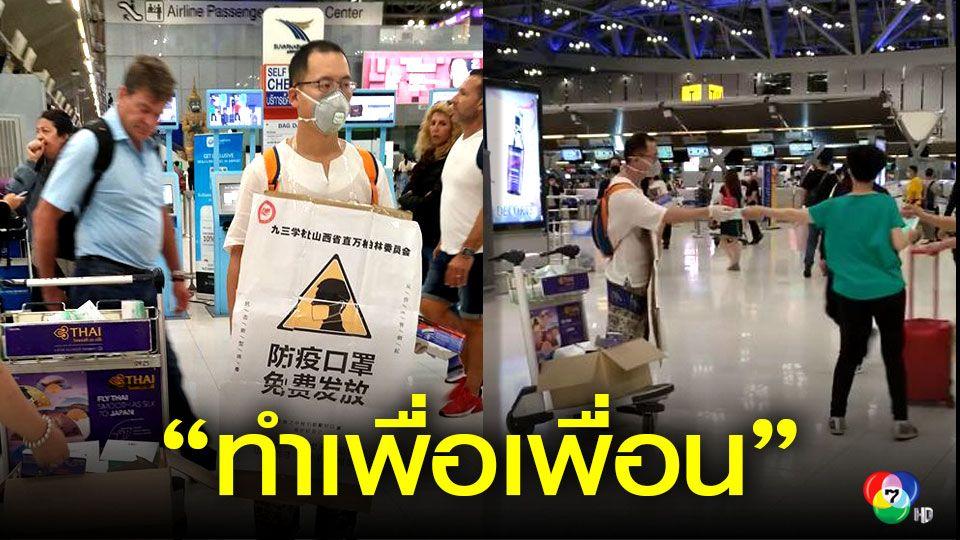 ชาวจีนยืนแจกหน้ากากอนามัย ในสนามบินสุวรรณภูมิ